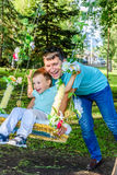Happy father pushing his son on a swing. In park Stock Photo
