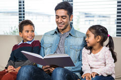Happy father reading a book for his children. In living room stock images