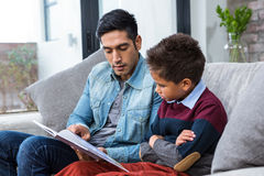 Happy father reading book with his son. In living room royalty free stock image