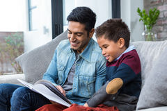 Happy father reading book with his son. In living room stock image