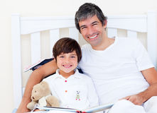 Happy father reading with his son. Sitting on a bed stock photography