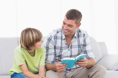 Happy father reading story for boy on sofa Royalty Free Stock Photos