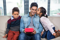 Happy father receiving a gift from his children Stock Images