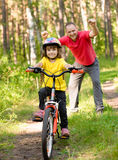 Happy father rejoices that her daughter learned to ride a bike.  Stock Photos
