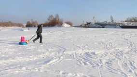 Happy father rolls his little daughter on snowtube at frozen river near ships stock video