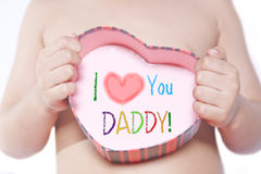 Happy Father's Day. Toddler holding a heart shaped box with with writings isolated on white Royalty Free Stock Images