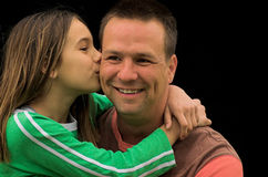 Happy Father's Day. A young girl giving her father a kiss on the cheek stock photos