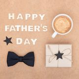 Happy Father`s Day Background. Cup of coffee, beautiful present and black bow tie on brown background flat lay. Fathers day. Happy Father`s Day Background. Cup Royalty Free Stock Photos