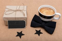 Father`s Day Background. Cup of coffee, beautiful present and black bow tie on brown background flat lay. Fathers day. Happy Father`s Day Background. Cup of Stock Photos