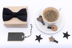 Happy Father`s Day Background. Cup of coffee, beautiful present and black bow tie on white background flat lay. Fathers day still life setup Royalty Free Stock Photo