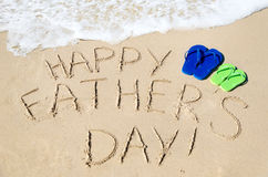 Happy father's day background. With flip flops on the sandy beach Royalty Free Stock Photo