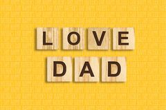 Happy father`s day background. Love Dad Word, written on wooden blocks. Yellow background Congratulatory background. Festive background stock illustration