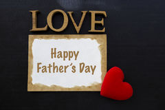 Happy Father`s day card concept. On black background, Love wooden text and old card with red heart Royalty Free Stock Photography