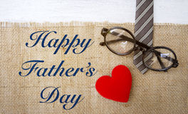 Happy Father`s day card concept. Eyeglasses on necktie with red heart on hessian texture background Royalty Free Stock Images