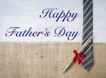 Happy Father`s day card concept. New pen gift on necktie over hessian background Royalty Free Stock Photography