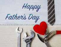 Happy Father`s day card concept. Pliers with red heart and necktie on white wood table background Royalty Free Stock Photos