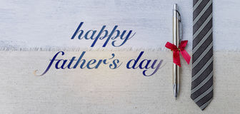 Happy father`s day card concept. Silver pen and black necktie on canvas background Royalty Free Stock Photos