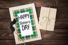 Happy Father`s Day card and gift box. On wooden table Royalty Free Stock Photos