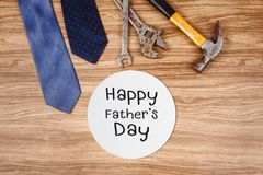 Happy Father`s Day card with old rusty tools and tie. On wooden background royalty free stock image