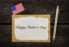 Happy Father`s day card on vintage wood background. With American flag and silver pen Stock Photo