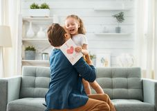 Happy father`s day. ! Child daughter congratulating dad and giving him postcard. Daddy and girl smiling and hugging. Family holiday and togetherness stock image