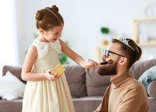 Happy father`s day! child daughter in crown does makeup to daddy stock photo