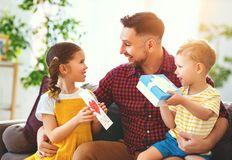 Happy father`s day! Children congratulates dad and gives him gift and postcard stock photo