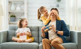 Daughters congratulating dad. Happy father`s day! Children daughters congratulating dad and giving him gift box. Daddy and girls smiling and hugging. Family stock photos