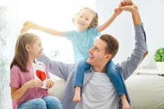 Happy father`s day. ! Children daughters congratulating dad and giving him postcard. Daddy and girls smiling and hugging. Family holiday and togetherness stock photo