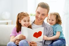 Happy father`s day. ! Children daughters congratulating dad and giving him postcard. Daddy and girls smiling and hugging. Family holiday and togetherness royalty free stock photos