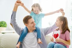 Happy father`s day. ! Children daughters congratulating dad and giving him postcard. Daddy and girls smiling and hugging. Family holiday and togetherness stock image