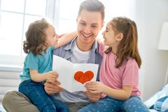 Happy father`s day. ! Children daughters congratulating dad and giving him postcard. Daddy and girls smiling and hugging. Family holiday and togetherness royalty free stock photography