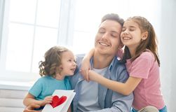 Happy father`s day. ! Children daughters congratulating dad and giving him postcard. Daddy and girls smiling and hugging. Family holiday and togetherness stock photos