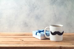 Happy Father`s day concept with coffee mug and gift box. Over wooden background stock photo