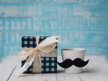 Happy father`s day concept. gift box, a cup of coffee with musta. Che on white and blue background stock photography