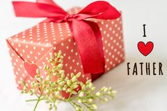 Happy father`s day concept. Gift box and flower, paper tag with I LOVE FATHER text Stock Image