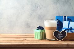 Happy Father`s day concept with latte macchiato coffee and gift box. Over wooden background stock image