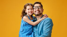 Happy father`s day! cute dad and daughter hugging on yellow background stock photos