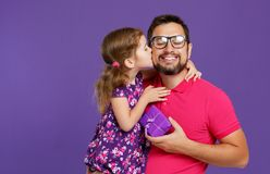 Happy father`s day! cute dad and daughter hugging on violet back. Happy father`s day! cute dad and daughter hugging on colored violet background royalty free stock photo