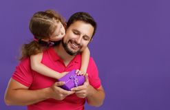 Happy father`s day! cute dad and daughter hugging on violet back Royalty Free Stock Photos