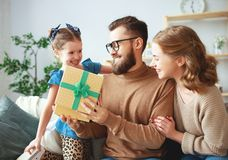 Happy father`s day! family mom and daughter congratulate dad and give gift stock photo