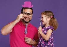 Happy father`s day! funny dad and daughter with mustache fooling. Around on colored purple background royalty free stock image