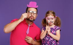 Happy father`s day! funny dad and daughter with mustache fooling. Around on colored purple background stock images