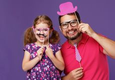 Happy father`s day! funny dad and daughter with mustache fooling. Around on colored purple background stock image