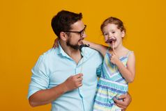 Happy father`s day! funny dad and daughter with mustache fooling. Around on colored yellow background Royalty Free Stock Photo