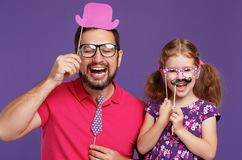 Happy father`s day! funny dad and daughter with mustache fooling. Around on colored purple background royalty free stock photography