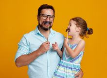 Happy father`s day! funny dad and daughter with mustache fooling. Around on colored yellow background stock photos