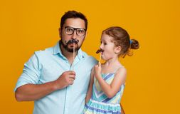 Happy father`s day! funny dad and daughter with mustache fooling. Around on colored yellow background royalty free stock image