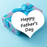 Happy father's day. Gift box with happy father's day greeting card over blue background Royalty Free Stock Images