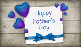 Happy Father's Day greeting card. With blue hearts and ribbon over wooden background stock photos